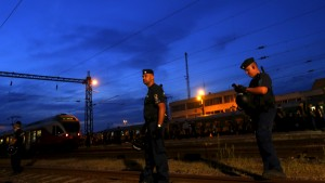 Police guard a train full of refugees stuck in a stalemate as they refuse to obey police and get off at the station, fearing they would be put up in a nearby refugee camp in Bicske, Hungary, September 3, 2015. France and Germany said European countries must be required to accept their shares of refugees, proposing what would potentially be the biggest change to the continent's asylum rules since World War Two. Europe's worst refugee crisis since the Yugoslav wars of the 1990s has strained the European Union's asylum system to breaking point, dividing its 28 nations and feeding the rise of right-wing populists. REUTERS/Laszlo Balogh - RTX1QZD1