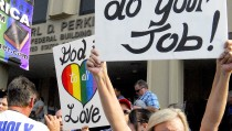 Lana Bailey holds a placard on the steps of the federal building in protest of Rowan County clerk Kim Davis' arrival to attend a contempt of court hearing for her refusal to issue marriage certificates to same-sex couples, at the United States District Court in Ashland, Kentucky September 3, 2015. REUTERS/Chris Tilley - RTX1R074