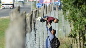 Migrants cross the fence to leave a migrant reception centre in Roszke, Hungary, September 4, 2015. Some 300 migrants broke out of a Hungarian border camp on Friday and hundreds of others set off on foot from Budapest as police scrambled to keep control of a migrant crisis that has brought Europe's asylum system to breaking point. REUTERS/Stringer  - RTX1R4TT