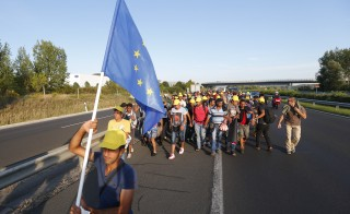 Migrants march along the highway towards the border with Austria, out of Budapest, Hungary, September 4, 2015. Hundreds of migrants broke out of a Hungarian border camp on Friday and others set off on foot from Budapest as authorities scrambled to contain a migrant crisis that has brought Europe's asylum system to breaking point. REUTERS/Laszlo Balogh   - RTX1R54R