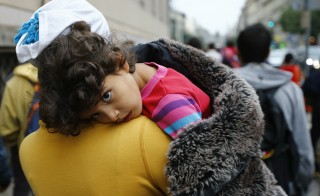 A migrant women holds her child as she walks down the street from Keleti train station in Budapest, Hungary, September 5, 2015. Several hundred migrants left Budapest's Keleti railway station on foot on Saturday and plan to walk to Vienna, a day after about a 1,000 migrants set off on a similar journey. Hungary sent about 4,500 migrants to the Austrian border by bus overnight, including those who were walking on the motorway, but said this was a one-off and there would be no further transports.    REUTERS/Leonhard Foeger - RTX1R7YZ