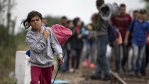 Rubi, 7, from Kobani, Syria walks along a railway track after crossing into Hungary from the border with Serbia near the village of Roszke September 5, 2015. Austria and Germany threw open their borders to thousands of exhausted migrants on Saturday, bussed to the Hungarian border by a right-wing government that had tried to stop them but was overwhelmed by the sheer numbers reaching Europe's frontiers. REUTERS/Marko Djurica - RTX1R81D