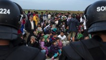 Migrants from Syria sit in front of riot police on a field after crossing into Hungary from the border with Serbia near the village of Roszke, September 5, 2015. Austria and Germany threw open their borders to thousands of exhausted migrants on Saturday, bussed to the Hungarian border by a right-wing government that had tried to stop them but was overwhelmed by the sheer numbers reaching Europe's frontiers.   REUTERS/Marko Djurica      TPX IMAGES OF THE DAY      - RTX1R9K4