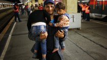 A migrant carries his children at the railway station in Vienna, Austria, September 5, 2015. Austria and Germany threw open their borders to thousands of exhausted migrants on Saturday, bussed to the Hungarian border by a right-wing government that had tried to stop them but was overwhelmed by the sheer numbers reaching Europe's frontiers.    REUTERS/Leonhard Foeger  - RTX1R9YA
