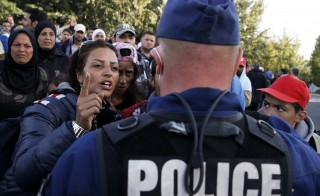 Migrants address a Hungarian police officer at collection point in the village of Roszke, Hungary, September 7, 2015. Police used pepper spray on a crowd of migrants attempting to break through a cordon at Roszke, on Hungary's border with Serbia, on Monday, a Reuters witness said.         REUTERS/Marko Djurica  - RTX1RIUB