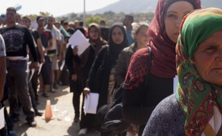 Refugees and migrants line up inside a soccer stadium used as a registration centre at the city of Mytilene, on the Greek island of Lesbos, September 8, 2015. Greece asked the European Union for aid to prevent it being overwhelmed by refugees, as a minister said arrivals on Lesbos had swollen to three times as many as the island could handle.  REUTERS/Dimitris Michalakis - RTX1RMCL