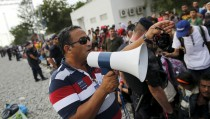 Nizar Shoukry speaks through a megaphone at railway station in Tovarnik, Croatia, September 19, 2015.  Love brought Nizar Shoukry from his native Syria to Croatia and eventually a dental practice in the border town of Tovarnik. Thirty years later, war is bringing his countrymen, in a chaotic, desperate tide flowing past Shoukry's door en route to Germany and a promise of asylum. Picture taken September 19, 2015. REUTERS/Antonio Bronic - RTX1RRUK