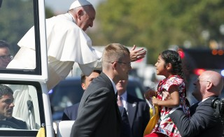 Pope Francis reaches for a child during a parade in Washington, D.C., on Sept. 23. Photo by Alex Brandon/Pool  via Reuters