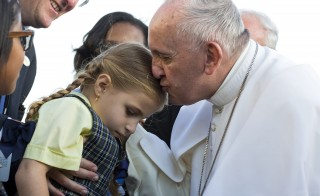 Pope Francis kisses Maria Teresa Heyer, a first grade student from Brooklyn, as he arrives at John F. Kennedy International Airport on Sept. 24 in New York. The pope is on a five-day trip to the United States, which includes stops in Washington D.C., New York and Philadelphia, after a three-day stay in Cuba. Photo by Craig Ruttle/AP/Pool via Reuters