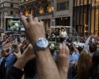 Pope Francis waves from his vehicle as he is driven down 5th avenue near St. Patrick's Cathedral in New York September 24, 2015.  REUTERS/Lucas Jackson  - RTX1SCBB