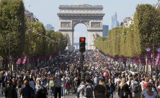 People walk on the Champs-Elysees, September 27, 2015 as central Paris goes car-free on Sunday. The French capital's central arrondissements and areas around landmarks such as the Eiffel Tower and Champs-Elysees are free from car noise and exhaust fumes, allowing people to stroll, cycle or skate between 0900 GMT and 1600 GMT.  REUTERS/Philippe Wojazer   - RTX1SPIQ