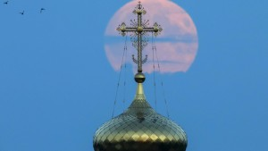 "A cross atop of a local monastery stands in front of the moon in the settlement of Poschupovo in Ryazan region, Russia, September 27, 2015. Sky-watchers around the world are in for a treat Sunday night and Monday when the shadow of Earth casts a reddish glow on the moon, the result of rare combination of an eclipse with the closest full moon of the year. The total ""supermoon"" lunar eclipse, also known as a ""blood moon"" is one that appears bigger and brighter than usual as it reaches the point in its orbit that is closest to Earth. REUTERS/Maxim Shemetov - RTX1SQO8"