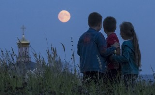 Children gather in Poschupovo in the Ryazan region of Russia to look at the full moon on Sept. 27. Photo by Maxim Shemetov/Reuters