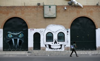 A boy walks past graffiti painted by pro-Houthi activists on the gate of the Saudi embassy in Yemen's capital Sanaa August 31, 2015. Saudi Arabian forces have made repeated small incursions across the border with Yemen in response to attacks since the start of airstrikes against Houthi forces on March 26, the Saudi-led coalition said on Sunday. REUTERS/Khaled Abdullah - RTX1QH96