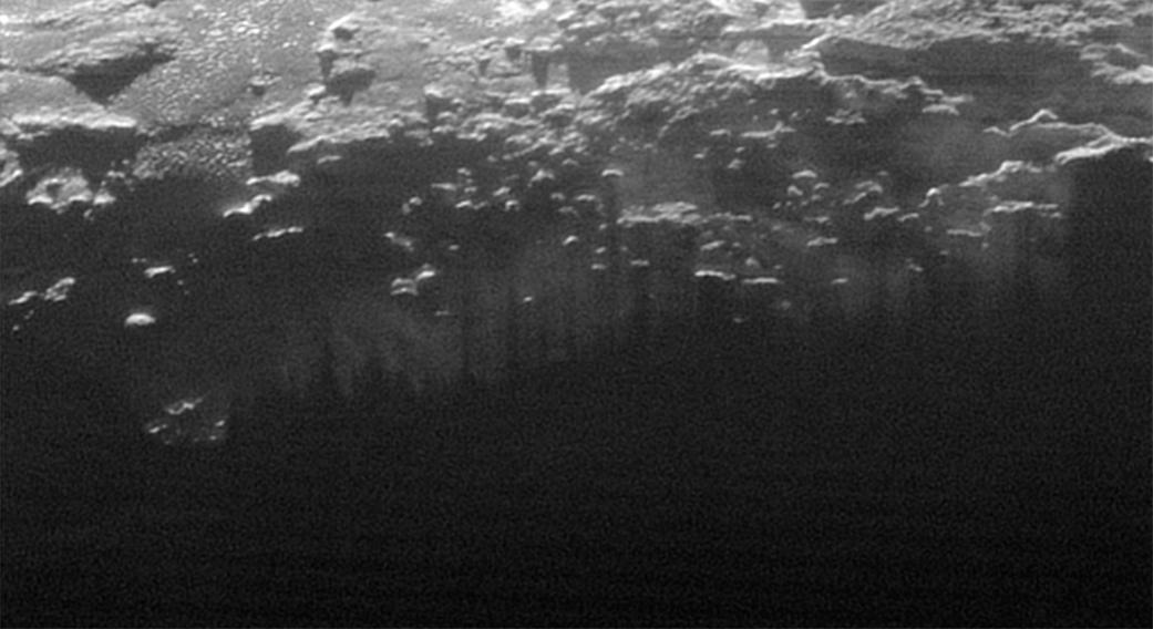 Shadows of various small mountains on the surface of Pluto cut through the haze. Image courtesy of NASA/JHUAPL/SwRI