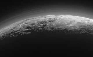 Just 15 minutes after its closest approach to Pluto on July 14, 2015, NASA's New Horizons spacecraft looked back toward the sun and captured this near-sunset view of the rugged, icy mountains and flat ice plains extending to Pluto's horizon. The image was taken from a distance of 11,000 miles to Pluto; the scene is 780 miles wide. Image courtesy of NASA/JHUAPL/SwRI