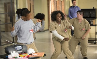 From left to right: Poussey Washington (Samira Wiley), Tasha 'Taystee' Jefferson (Danielle Brooks), Big Boo (Lea DeLaria), and George 'Pornstache' Mendez (Pablo Schreiber) in ORANGE IS THE NEW BLACK. Photo courtesy of Lionsgate Publicity