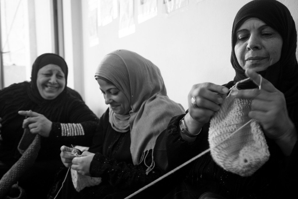 Three women sew at Basmeh & Zeitooneh in Shatila, Lebanon, in 2014. Photo by Youssef Shoufan