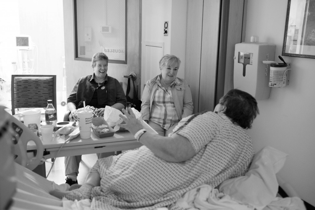 "Carol with her friends Kelly, left, and Tina, right. after being admitted for treatment for heart disease at Mount Sinai Hospital, Long Island City, New York City. ""My last three years in prison I spent on the RMU [Regional Medical Unit]. It's like a mini hospital, but it's really isolating. It's worse than solitary. No one can visit you because everyone's in their programs during scheduled visiting hours and you can't get permission to leave your program. I could see my friends from the screened-in porch but I couldn't talk to them because you're not allowed to holler."" Photo and caption by Sara Bennett"