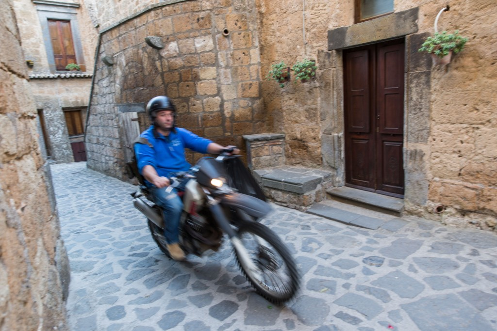 No cars are allowed in Civita di Bagnoregio due to the fragile nature of the landscape, so a man on a motorcycle must suffice for a garbage truck. Photo by Frank Carlson