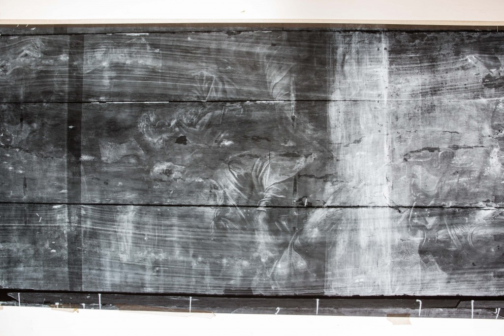 """A large x-ray shows one panel of Giorgio Vasari's """"Last Supper,"""" including where the splits in its wood planks occurred and where paint was lost. Photo by Frank Carlson"""