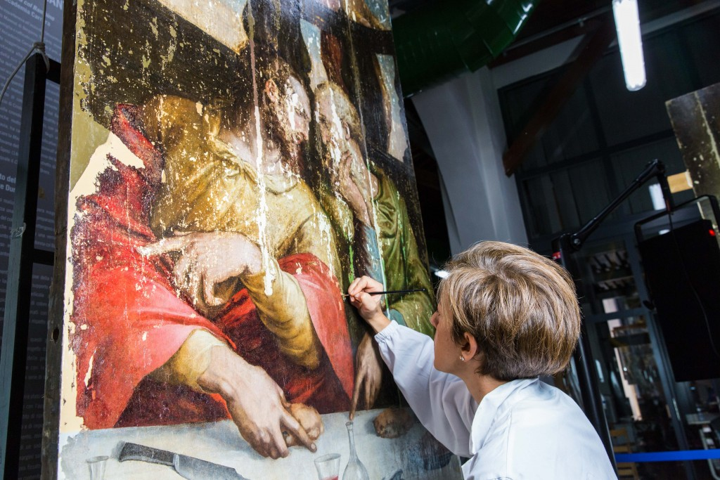 """A conservator works on a panel of Giorgio Vasari's """"Last Supper,"""" which the Opificio delle Pietre Dure is now restoring, nearly 50 years after it was damaged by a flood. Photo by Frank Carlson"""