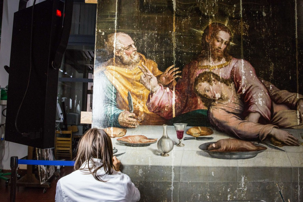 """Another restorer works on the central panel of Vasari's """"Last Supper."""" The painting sat in storage for more than 40 years after the 1966 flood while experts developed the skills and confidence to restore it in one piece. Photo by Frank Carlson"""