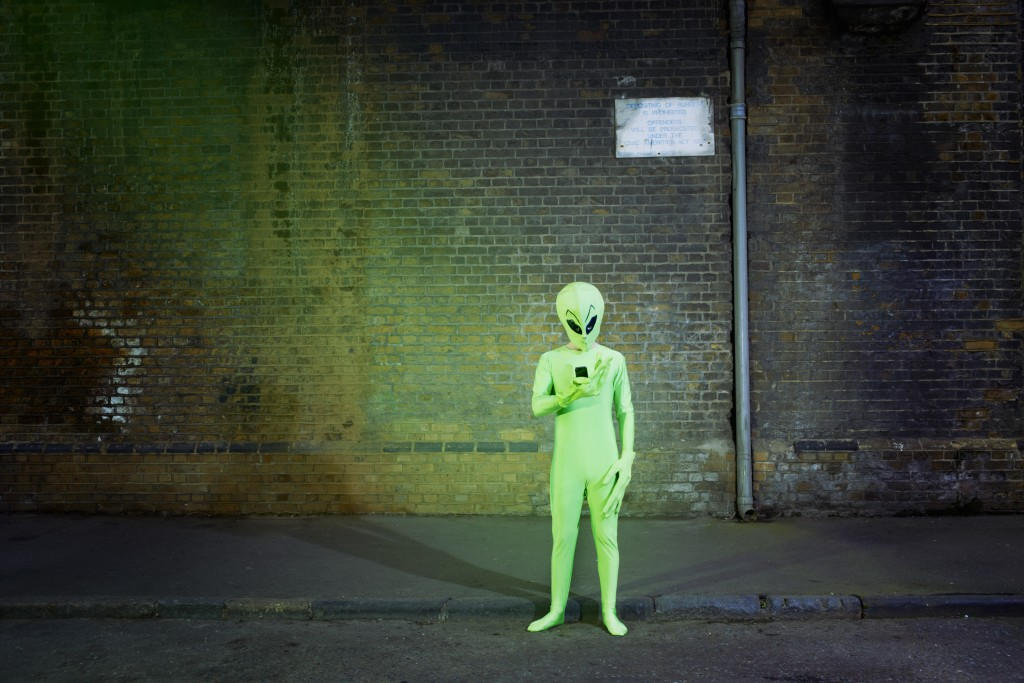 times that science explained aliens newshour man dressed in alien costume looking at mobile photo by tara moore