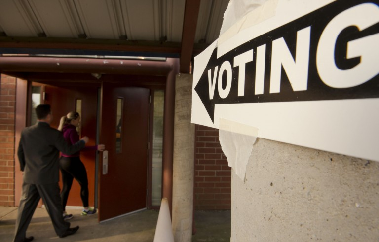 CHARLOTTE, NC - NOVEMBER 4:   People enter First Ward Elementary School to cast their votes on November 4, 2014, in Charlotte, North Carolina. Americans head to the polls to cast their vote in the mid-term elections which will ultimately decide what party controls the U.S. Senate.  (Photo by Davis Turner/Getty Images)