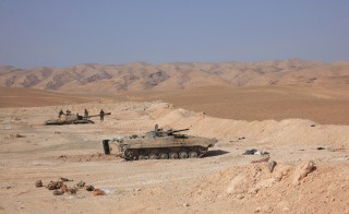 Tanks belonging to Syrian government forces are positioned near the Jazel oil field, near the ancient city of Palmyra in the east of Homs province after they retook the area from Islamic State (IS) group fighters on March 9, 2015. Recent US-led coalition air strikes have frequently targeted oil facilities run by the IS group jihadists, who according to some estimates earn more than $1 million per day from oil sales. AFP PHOTO/ STR        (Photo credit should read STR/AFP/Getty Images)
