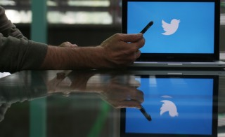 An Apple Inc. iPhone 6 smartphone is held as a laptop screen shows the Twitter Inc. logo in this arranged photograph taken in London, U.K., on Friday, May, 15, 2015. Facebook Inc. reached a deal with New York Times Co. and eight other media outlets to post stories directly to the social network's mobile news feeds, as publishers strive for new ways to expand their reach. Photographer: Chris Ratcliffe/Bloomberg via Getty Images