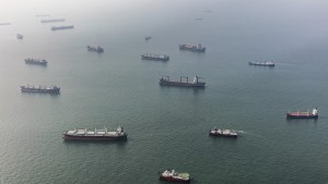 Ships sit offshore in the Singapore Strait in this aerial photograph taken above Singapore, on Thursday, July 2, 2015. Singapore's economy contracted more than analysts predicted last quarter, underscoring the weakening outlook for Asian nations amid sluggish global growth. The local dollar weakened to its lowest level in more than a month. Photographer: Darren Soh/Bloomberg via Getty Images