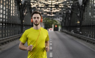 Young male athlete running on bridge wearing headphones