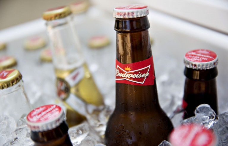 Bottles of Anheuser-Busch InBev NV Budweiser brand beer, right, are arranged for a photograph in a cooler alongside SABMiller Miller brand beer in Tiskilwa, Illinois, U.S., on Wednesday, Sept. 16, 2015. Anheuser-Busch InBev NV said it intends to make an offer for SABMiller Plc to unite the world's two biggest beermakers with brands including Budweiser and Peroni and create a company that would control about half the industry's profit. Photographer: Daniel Acker/Bloomberg via Getty Images