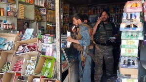 Afghan security personnel gather at a roadside shop in Kunduz on October 4, 2015, as Afghan forces, backed up by their NATO allies, claim to have wrestled back control of the city. President Barack Obama has promised a full investigation into an apparent US air strike on an Afghan hospital in Kunduz that killed 19 people, a bombing which the UN said could amount to a war crime.  The air raid came days after Taliban fighters seized control of the strategic northern city, in their most spectacular victory since being toppled from power by a US-led coalition in 2001.   AFP PHOTO/STR        (Photo credit should read STRDEL/AFP/Getty Images)