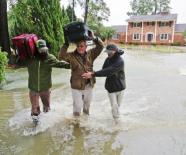 Mack Leppard, center, is helped by friends, neighbors and volunteers as they retrieve items from his flooded home on Woodlake Drive on Oct. 5, 2015 in Columbia, S.C. (Gerry Melendez/The State/TNS via Getty Images)