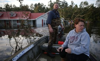 ANDREWS, SC - OCTOBER 09: Justin Lawshe (L) and Wendy Lawshe use a boat to check on her fathers home that is inundated by flood water coming from the breached dams upstream as the water continues to reach areas in the eastern part of the state on October 9, 2015 in Andrews, South Carolina.  The state of South Carolina experienced record rainfall amounts causing severe flooding and officials expect the damage from the flooding waters to be in the billions of dollars.  (Photo by Joe Raedle/Getty Images)