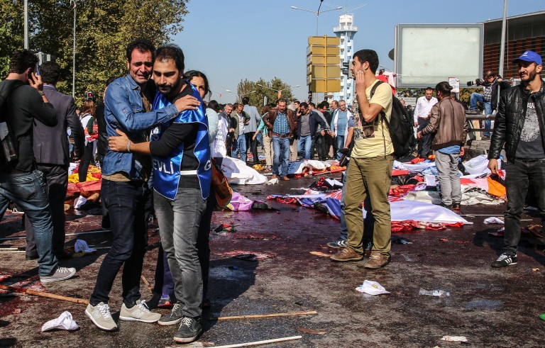 ANKARA, TURKEY - OCTOBER 10: (TURKEY OUT)  Survivors stand amongst the dead and injured at the blast scene after an explosion during a peace march in Ankara, October 10, 2015 Turkey. Turkish Health Minister says 86 people killed and 186 wounded in twin bomb blasts outside the main train station in the Turkish capital Ankara where people were gathering for a peace march. (Photo by Defne Karadeniz/Getty Images)
