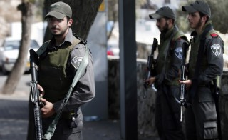 Israeli border policemen stand guard at a bus stop in the east Jerusalem Jewish settlement of Armon Hanatsiv, adjacent to the Palestinian neighbourhood of Jabal Mukaber, on October 18 2015. Israel pressed ahead with major security measures after five more stabbing incidents. Israel has set up checkpoints in Palestinian areas of east Jerusalem, where many of the knife attackers have come from, and hundreds of soldiers have reinforced their patrols, but frustrated youths have defied efforts to prevent violence. AFP PHOTO / THOMAS COEX        (Photo credit should read THOMAS COEX/AFP/Getty Images)