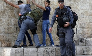 Israeli policemen check Palestinian youths at Damascus Gate in the Old City of Jerusalem on October 18, 2015 as security measures are increased. Israel rejected a proposal to send international observers to the to Jerusalem's Al-Aqsa mosque compound in a bid to calm unrest after five more stabbing incidents defied a security crackdown. AFP PHOTO / AHMAD GHARABLI        (Photo credit should read AHMAD GHARABLI/AFP/Getty Images)