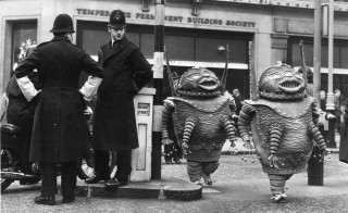Actors dressed as martians for their roles in the show 'The Man in the Moon', at the London Palladium in January 1964, walk across Regent Street as two policemen watch them. Photo by Chris Ware/via Getty Images