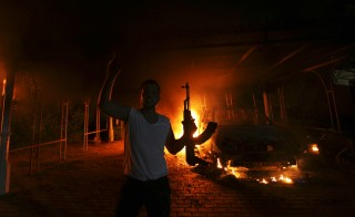 A protester reacts as the U.S. Consulate in Benghazi is seen in flames during a protest by an armed group said to have been protesting a film being produced in the United States September 11, 2012. An American staff member of the U.S. consulate in the eastern Libyan city of Benghazi has died following fierce clashes at the compound, Libyan security sources said on Wednesday. Armed gunmen attacked the compound on Tuesday evening, clashing with Libyan security forces before the latter withdrew as they came under heavy fire. REUTERS/Esam Al-Fetori (LIBYA - Tags: POLITICS CIVIL UNREST TPX IMAGES OF THE DAY) - RTR37UVH
