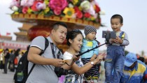 """A family takes a """"selfie"""" next to a boy in front of a giant basket of flowers on display at Tiananmen Square for the upcoming 65th National Day celebrations on Wednesday, in Beijing, September 29, 2014. REUTERS/Jason Lee (CHINA - Tags: POLITICS SOCIETY ANNIVERSARY) - RTR483MH"""