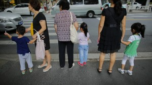Women hold childrens' hands as they wait to cross a street after school in downtown Shanghai September 12, 2014. REUTERS/Carlos Barria  (CHINA - Tags: SOCIETY POLITICS) - RTR494TM