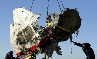 Local workers transport a piece of the Malaysia Airlines flight MH17 wreckage at the site of the plane crash near the village of Hrabove (Grabovo) in Donetsk region, eastern Ukraine, on Nov. 20, 2014. Photo by Antonio Bronic/Reuters