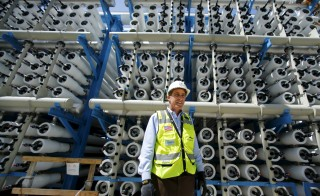 Poseidon Water project manager Peter MacLaggen stands next to some reverse osmosis filters as work continues on the Western Hemisphere's largest seawater desalination plant in Carlsbad, California, April 14, 2015. Desalination has emerged as a newly promising technology in California in the face of a record dry spell that has forced tough new conservation measures, depleted reservoirs and raised the costs of importing fresh water from elsewhere. The biggest ocean desalination plant in the Western Hemisphere, a $1 billion project under construction since 2012 on a coastal lagoon in the California city of Carlsbad, is nearly completed and due to open in November, delivering up to 50 million gallons of water a day to San Diego County. To match Feature USA-DESALINATION/CALIFORNIA REUTERS/Mike Blake - RTR4XD0D