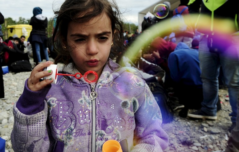 A migrant child blows soap bubbles at a transit camp in Gevgelija, Macedonia, after entering the country by crossing the border with Greece on Sept. 29, 2015. Photo by OgnenTeofilovski/Reuters