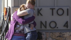 Umpqua Community College alumnus Donice Smith (L) is embraced after she said one of her former teachers was shot dead, near the site of a mass shooting at Umpqua Community College in Roseburg,Oregon October 1, 2015. A gunman opened fire at a community college in southern Oregon on Thursday, killing 13 people and wounding some 20 others before he was shot to death by police, state and county officials said, in the latest mass killing to rock a U.S. school. There were conflicting reports on the number of dead and wounded in the shooting rampage in Roseburg, which began shortly after 10:30 a.m. local time (1730 GMT).  REUTERS/Steve Dipaola - RTS2O4W