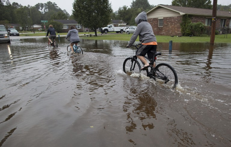 Children ride their bikes through flood waters on Rosewood Drive in Myrtle Beach, South Carolina October 5, 2015. Torrential rainfall that South Carolina's governor called a once-in-a-millennium downpour triggered flooding in the southeastern U.S. state on Sunday, causing at least eight deaths in the Carolinas. REUTERS/Randall Hill - RTS35F2
