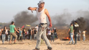 A Palestinian with blood on his clothes walks during clashes with Israeli troops near the border between Israel and Central Gaza Strip October 13, 2015. Seven Israelis and 28 Palestinians, including 10 alleged attackers and eight children, have died in almost two weeks of street attacks and security crackdowns. The violence has been stirred in part by Muslim anger over increasing Jewish visits to the al-Aqsa mosque compound in Jerusalem, Islam's holiest site outside the Arabian Peninsula. REUTERS/Ibraheem Abu Mustafa - RTS4ABD